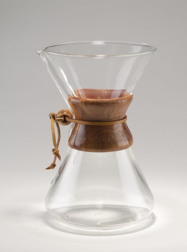 Cafetière en verre transparent. Cafetière en forme de sablier composée de deux cônes en verre inversés se réunissant au milieu en un col étroit autour duquel deux pièces de bois, faisant office de prise, sont enserrées par une lanière de cuir serrée par une boule de bois.