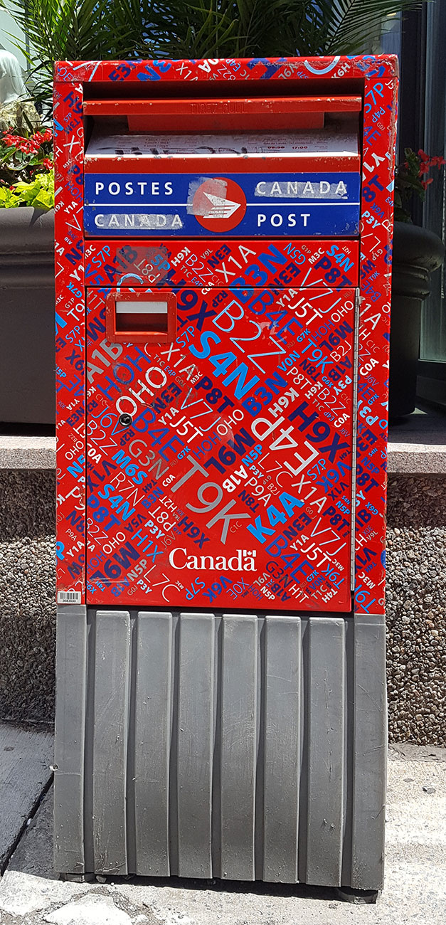 Rectangular Post Canada mailbox with a busy pattern made to deter graffiti.