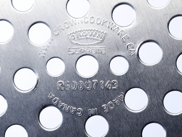 Close-up view of perforated metal pizza pan with manufacturer's markings.
