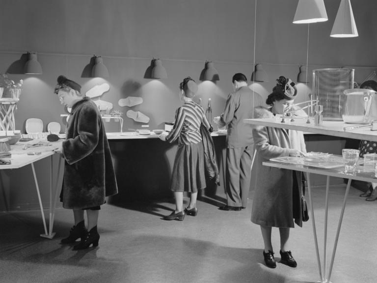 Photo noir et blanc d'une exposition. On voit des visiteurs du musée examinant des articles ménagers et d'autres objets disposés sur des tables.