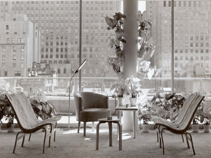 Black-and-white interior view of lounge area with a cluster of Working chairs and small tables with a view of New York City in the background.