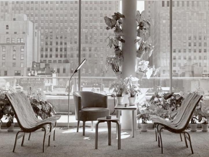 Image en noir et blanc d'un coin salon où sont disposées quelques chaises de travail et des tables basses. Vue sur la ville de NewYork en arrière-plan.