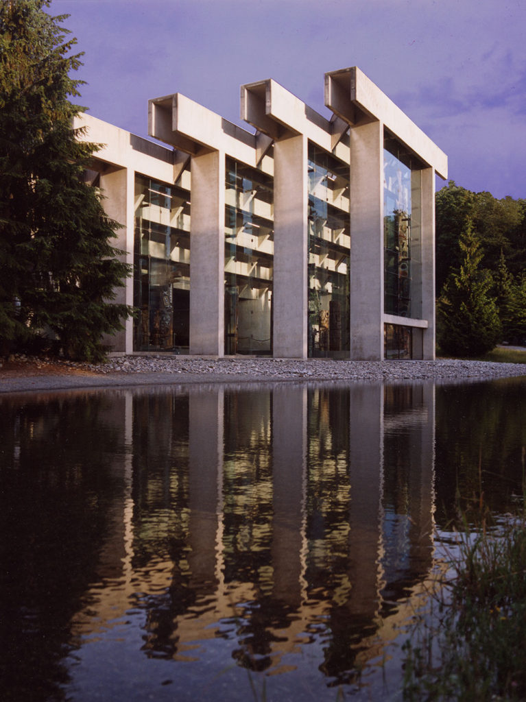 Concrete structure based on indigenous post-and-beam architecture with reflecting pool in front.