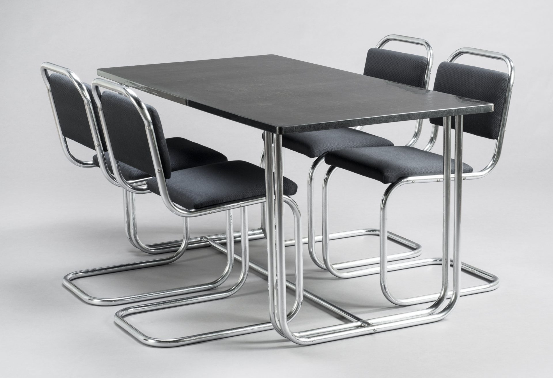 Dining table with four chairs. The table has a black Formica top and continuous bent-tubular-steel legs. The cantilevered chairs are also made of continuous tubes of steel with black-upholstered cushions.