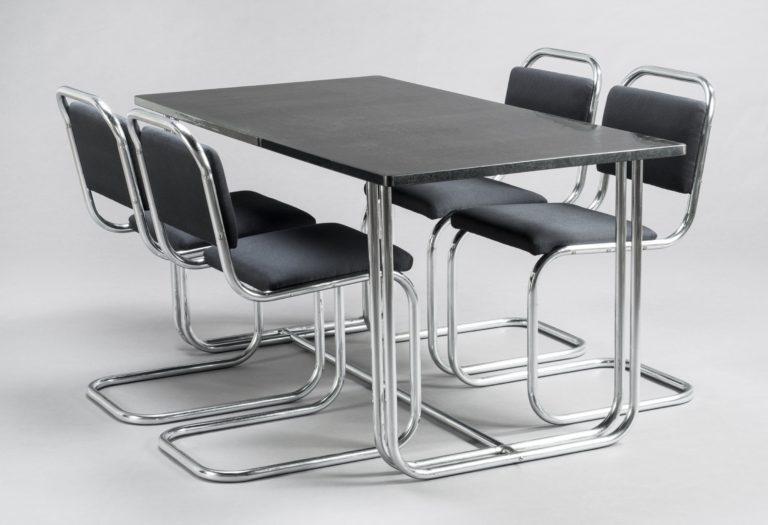 Table de salle à manger et quatre chaises. La table est dotée d'un plateau en Formica noir et de pieds monopièce en acier tubulaire courbé. Les chaises en porte-à-faux sont elles aussi faites d'acier tubulaire monopièce et dotées de coussins rembourrés noirs.