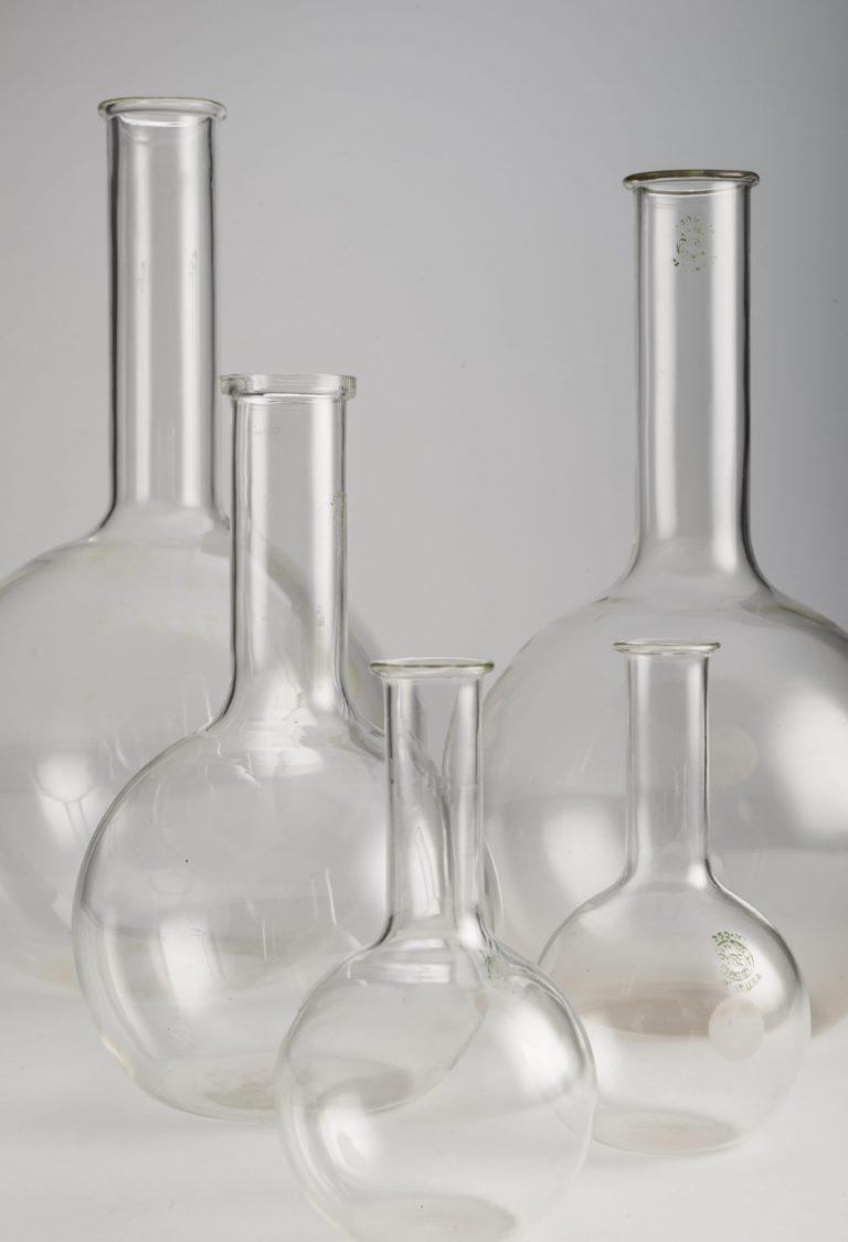 Cinq ballons de laboratoire à fond plat, tous en verre transparent, dotés d'une base sphérique et d'un col cylindrique. Deux ballons de 250ml, un de 1L, un de 2L et un de 3L
