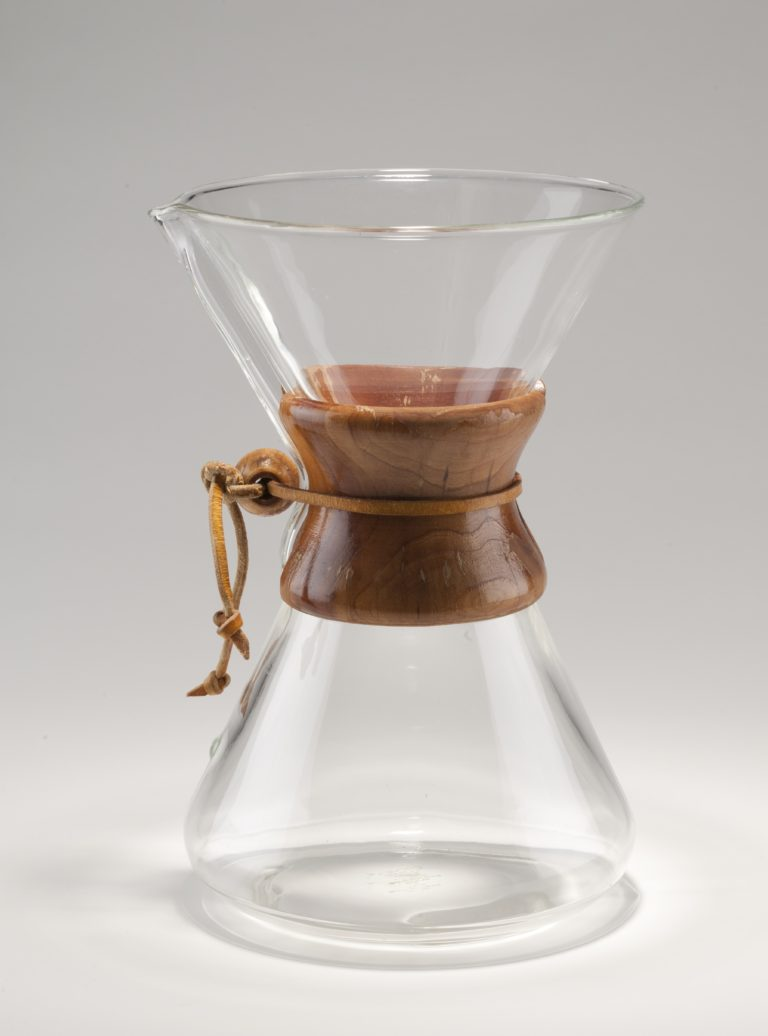 Transparent glass coffee maker. Its form is similar to an hourglass, with a glass cone shape for the bottom joined to another glass cone shape on the top, creating a narrow center  surrounded by a two-piece wooden handle held in place by a leather thong secured with a wooden bead.