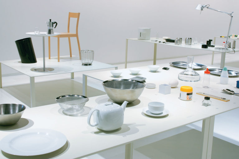 Exhibition installation view showing modern housewares and furniture arranged on white tables.