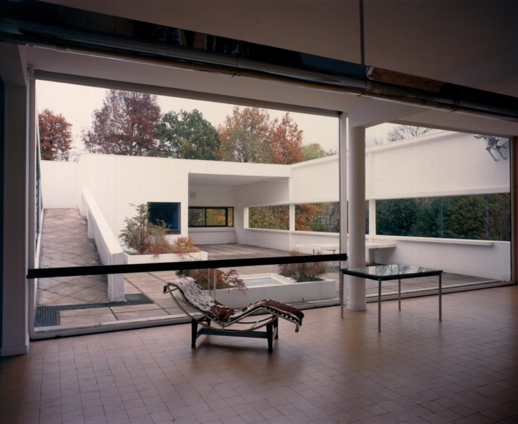 Interior view of modern house with courtyard visible in the background and a Corbusier chaise longue with brown-and-white cowhide upholstery and a table in the foreground.