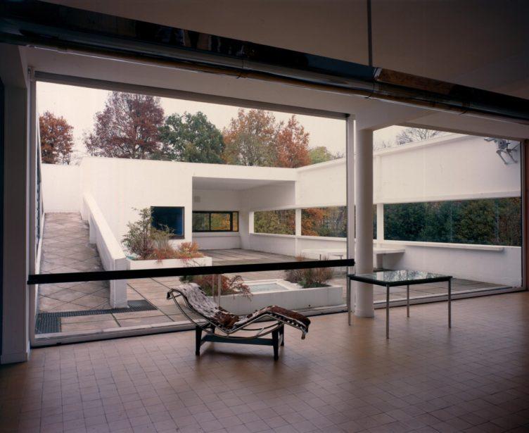 Vue intérieure d'une maison moderne avec cour en arrière-plan; chaise longue LeCorbusier garnie de cuir de vache brun et blanc et table au centre de la pièce.