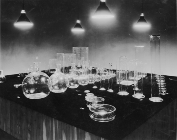 Black-and-white exhibition installation view showing numerous forms of laboratory glass, including flasks and cylinders, lined up according to size on a black cloth and lit from above.