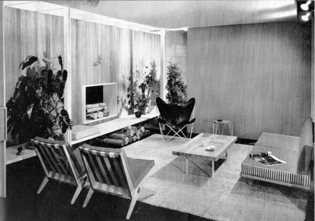Black-and-white exhibition installation view showing a living room display, including two Jeanneret chairs, a sofa, and a coffee table.