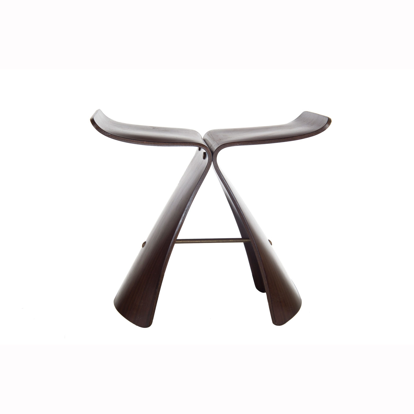 Wooden stool made of two identical pieces of bent wood connected by a slender bar in the base. Each piece of bent wood is shaped like a swooping numeral 7, with the one on the right turned backward.