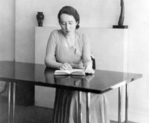 Black-and-white photo of Marga Barr seated and reading a book at a tubular steel dining table.