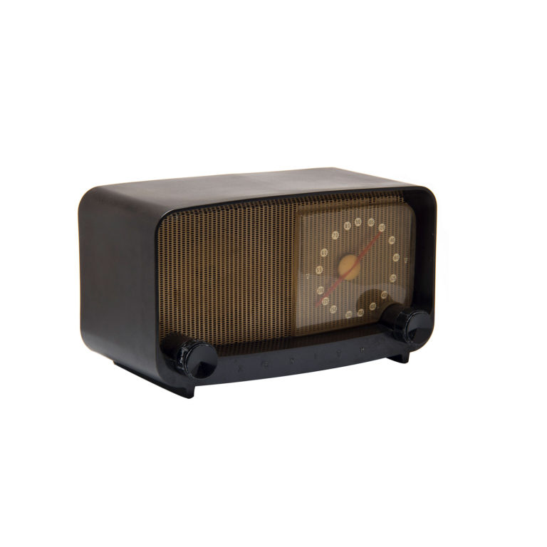 Rectangular table radio with dark brown plastic housing The housing has rounded corners and opens at the front to a gold-colored speaker and clear plastic radio dial with white number markers and a red needle.