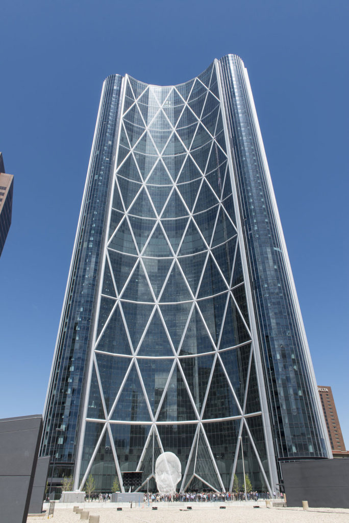 Skyscraper with crisscrossing white beams and glass walls. Front of the building is curved inward, partially surrounding a plaza with a white sculpture.