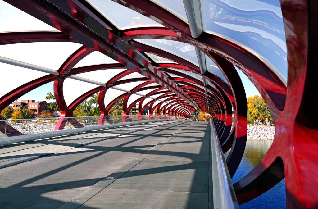Passerelle couverte ornée de croisillons rouges, de panneaux transparents et d'un revêtement de sol en asphalte noir.