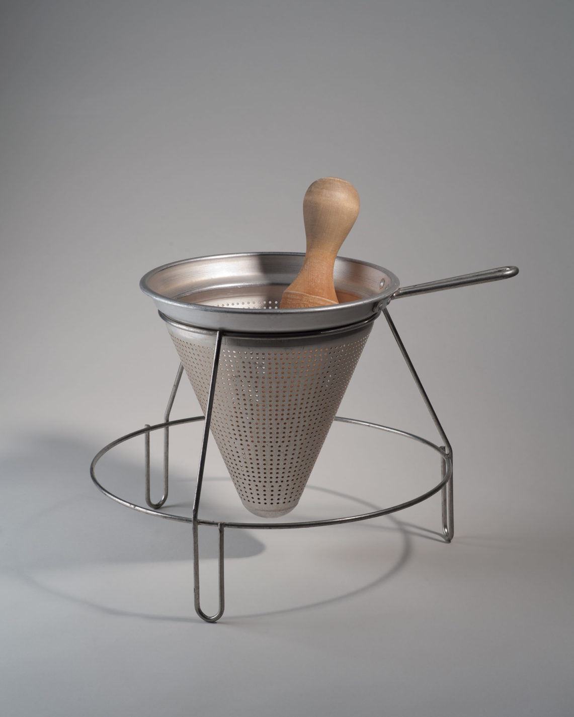 Conical sieve set into a circular wire frame with three legs and a handle. A wooden pestle sits inside the sieve.