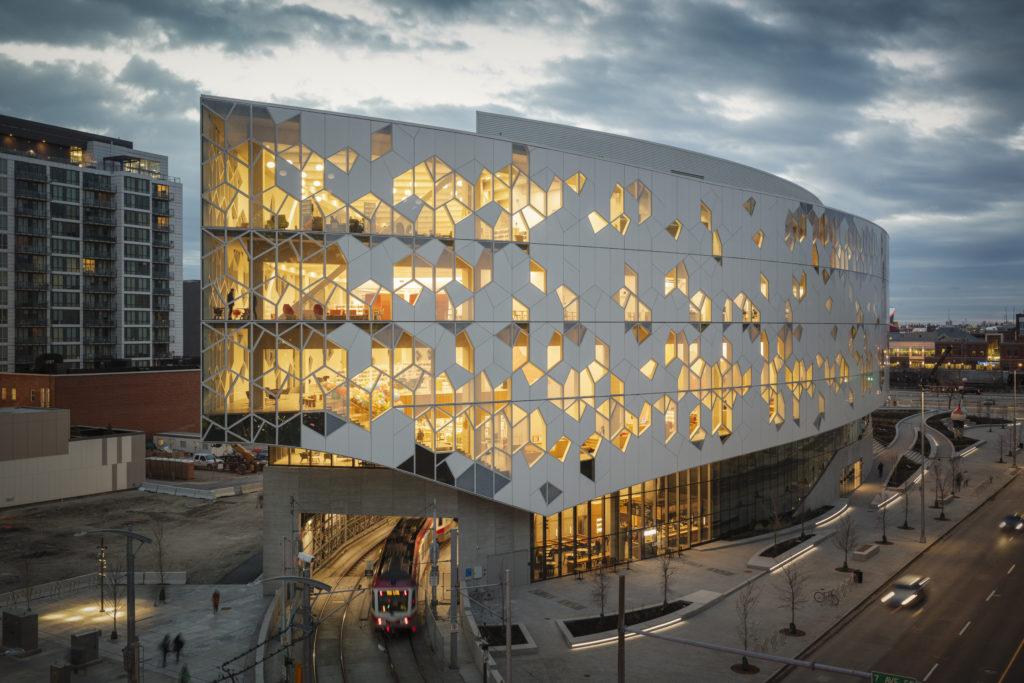 Bâtiment de forme elliptique occupant un îlot urbain. Murs de verre transparent et translucide, partiellement recouverts d'une matière blanche opaque.