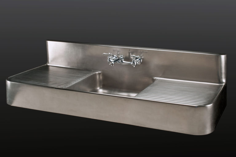 Wide metal sink with drainage boards on both sides of the rectangular basin and handles and faucet set at the center of a rectangular backsplash.