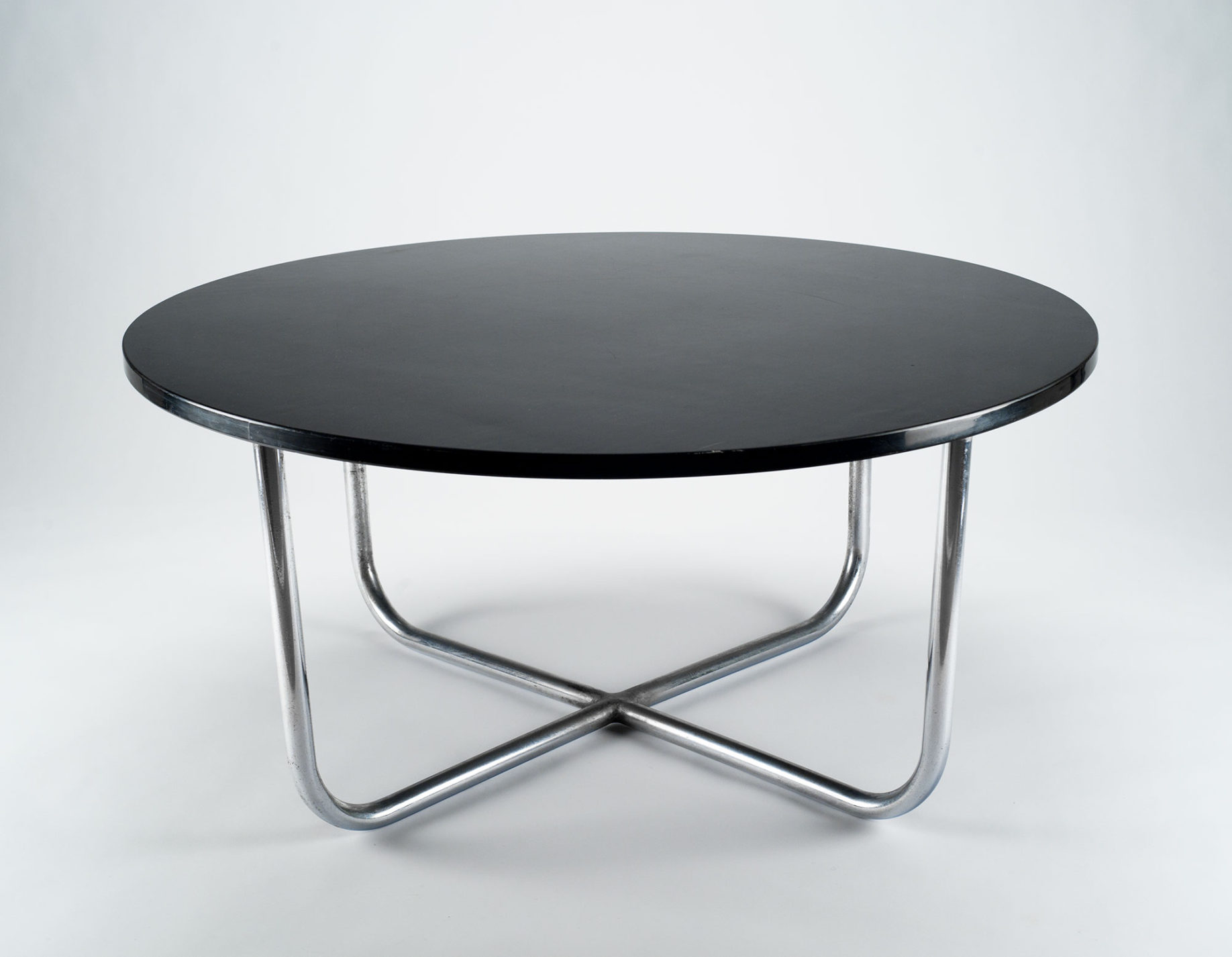 Coffee table. Circular black table top set on tubular steel legs that bend at the bottom and meet to form a cross at the center.