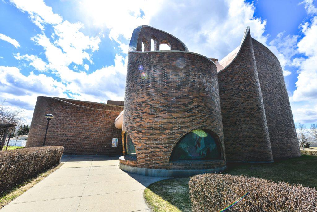 Église moderne en briques aux courbes harmonieuses.
