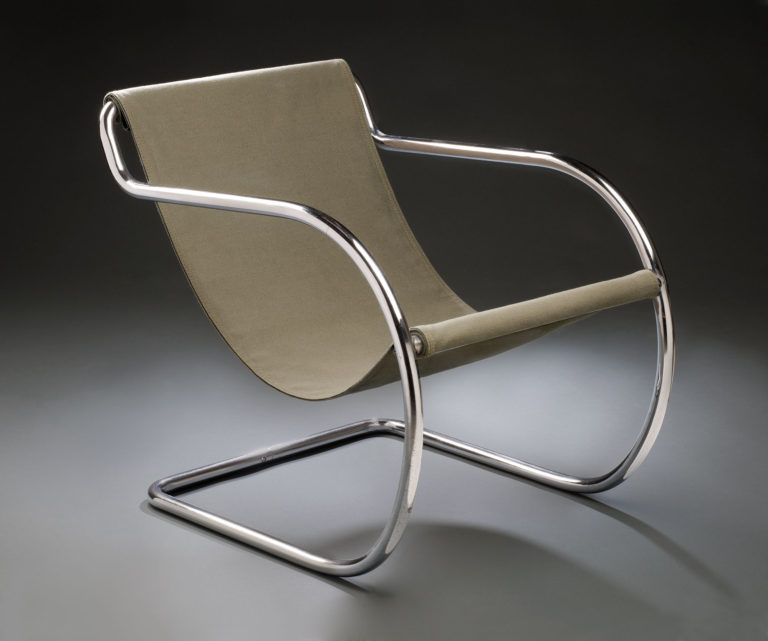Armchair with a frame made of a continuous piece of curving tubular steel and the seat and back made from a piece of fabric suspended between two bars.