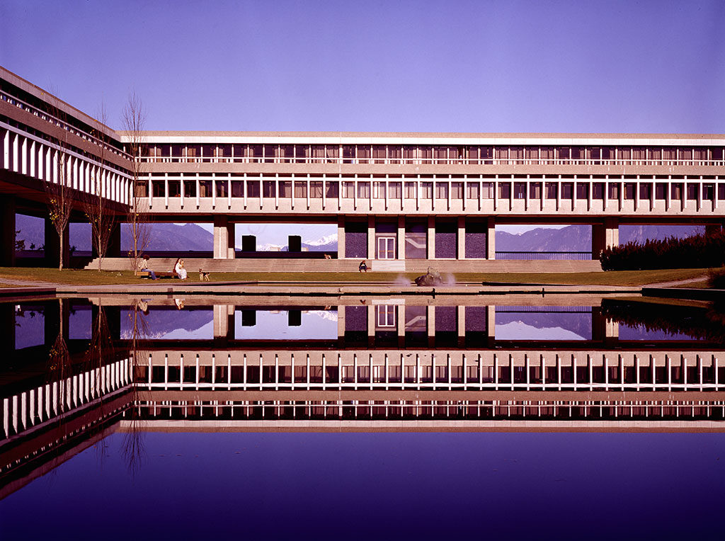 Long, low concrete and glass building elevated on columns and overlooking a pool of water.
