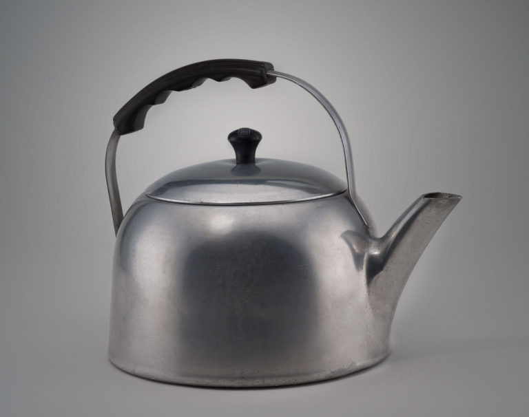Dome-shaped aluminum kettle with a short spout, a conforming metal lid with black finial, and a shaped black plastic grip on the arching handle above.