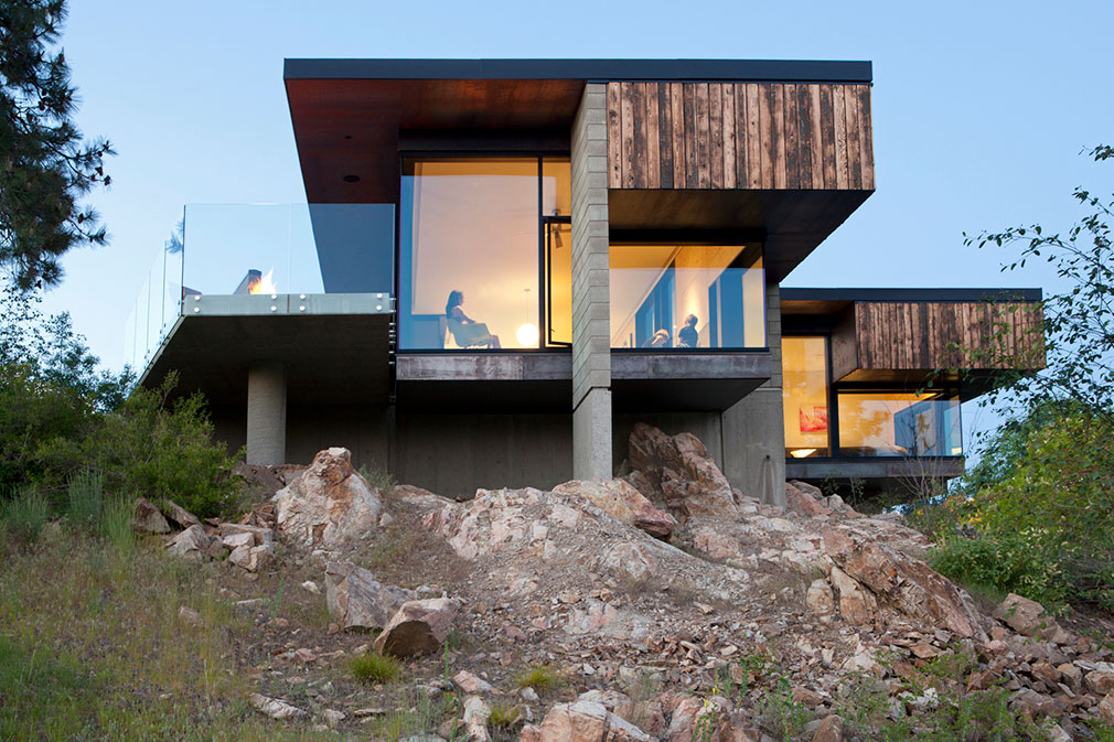 Stacked rectangular block forms made of wood, glass and concrete with cantilevered roof on a rocky hill.