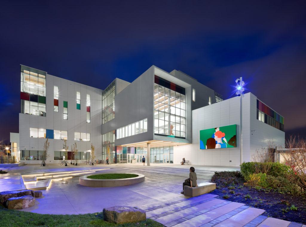 Bâtiment contemporain composé de grands blocs rectangulaires couvert de panneaux blancs et de verre et orné çà et là de panneaux aux couleurs vives. Une place est aménagée au pied du bâtiment.