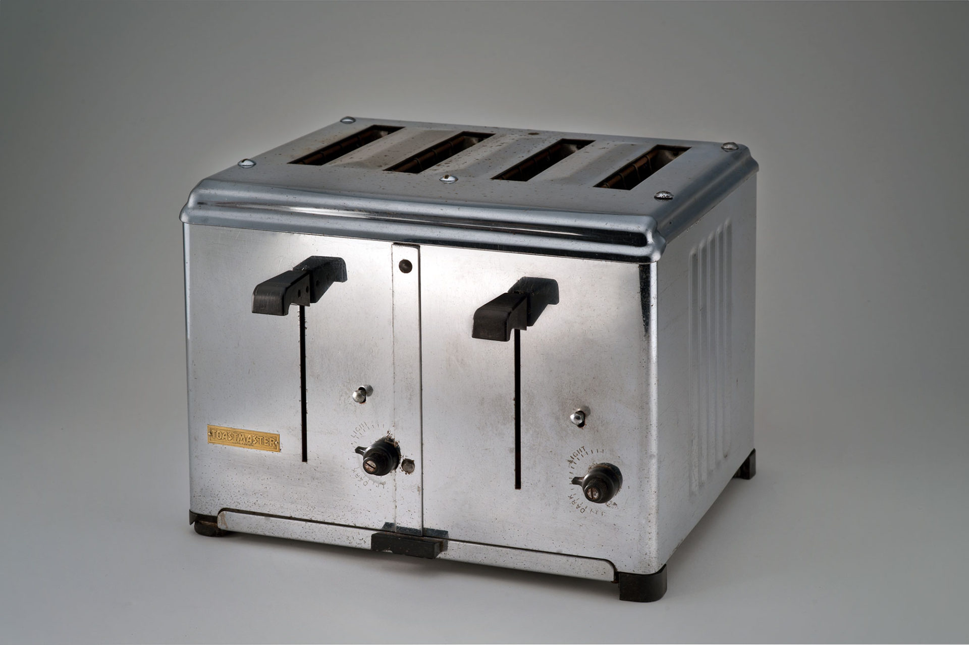 Box-shaped shiny metal toaster with openings for four slices of bread. It has two levers and two control knobs in black plastic on the front.