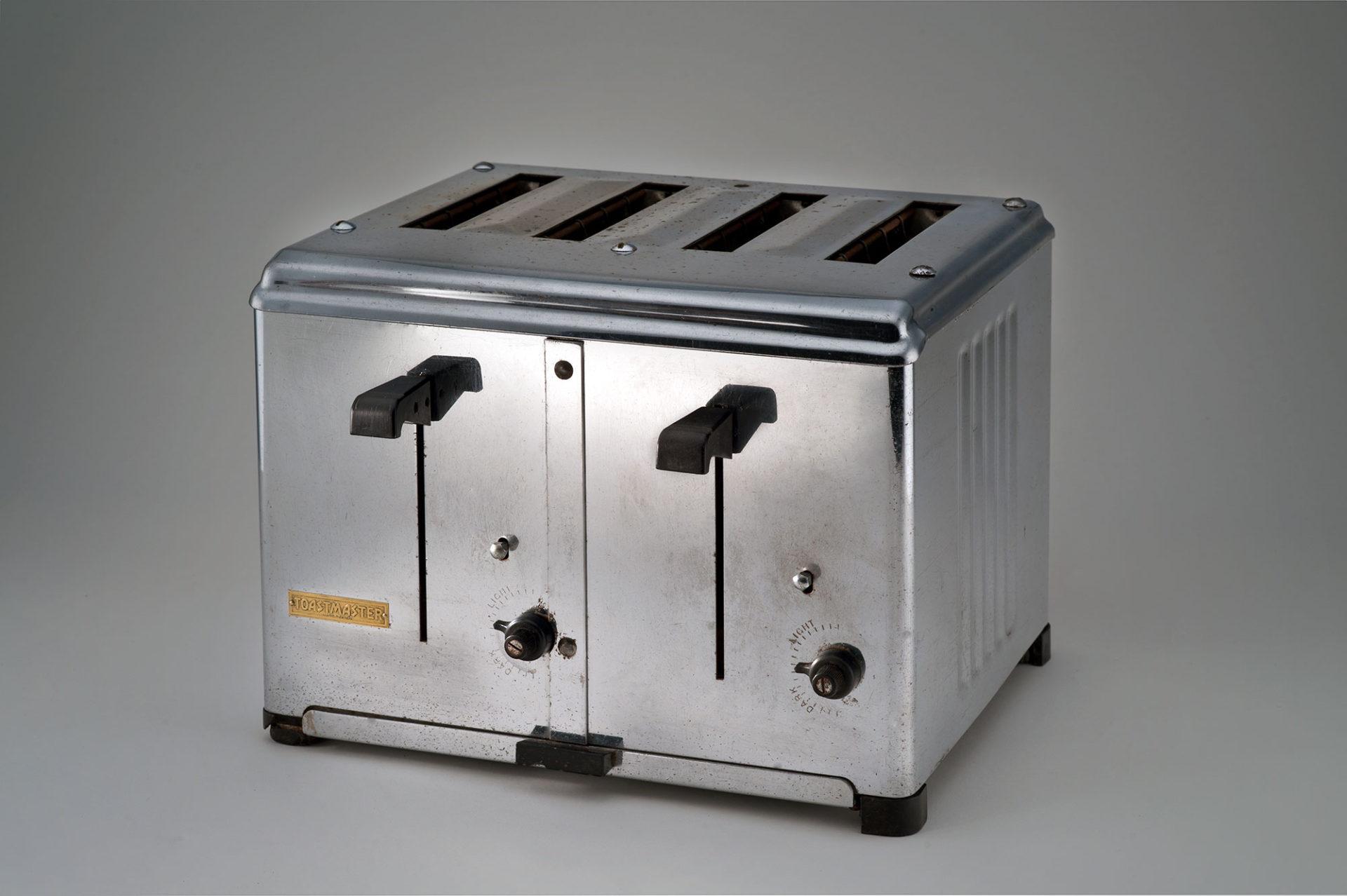 Grille-pain carré en métal lustré à quatre fentes. Sur le devant : deux leviers et deux boutons de réglage en plastique noir.