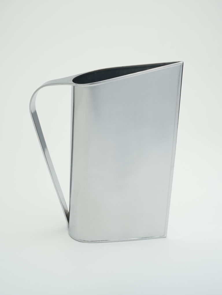 Shiny metal pitcher with teardrop-shaped footprint and a simple metal handle that connects at the top and bottom of the rounded side.