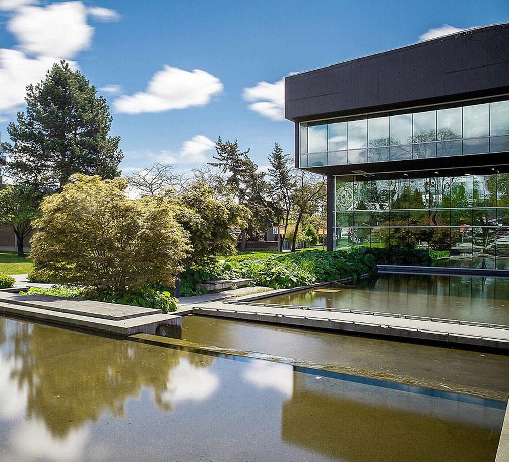 Bâtiment de forme rectangulaire irrégulière à trois étages en verre et en béton peint à côté d'un miroir d'eau.