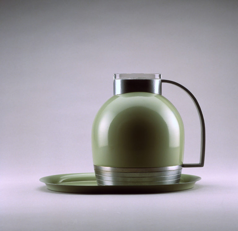 Dome-shaped thermal pitcher in green enameled metal with an aluminum base, top, and handle, and a lid of clear glass. It sits on an oval tray in matching green.