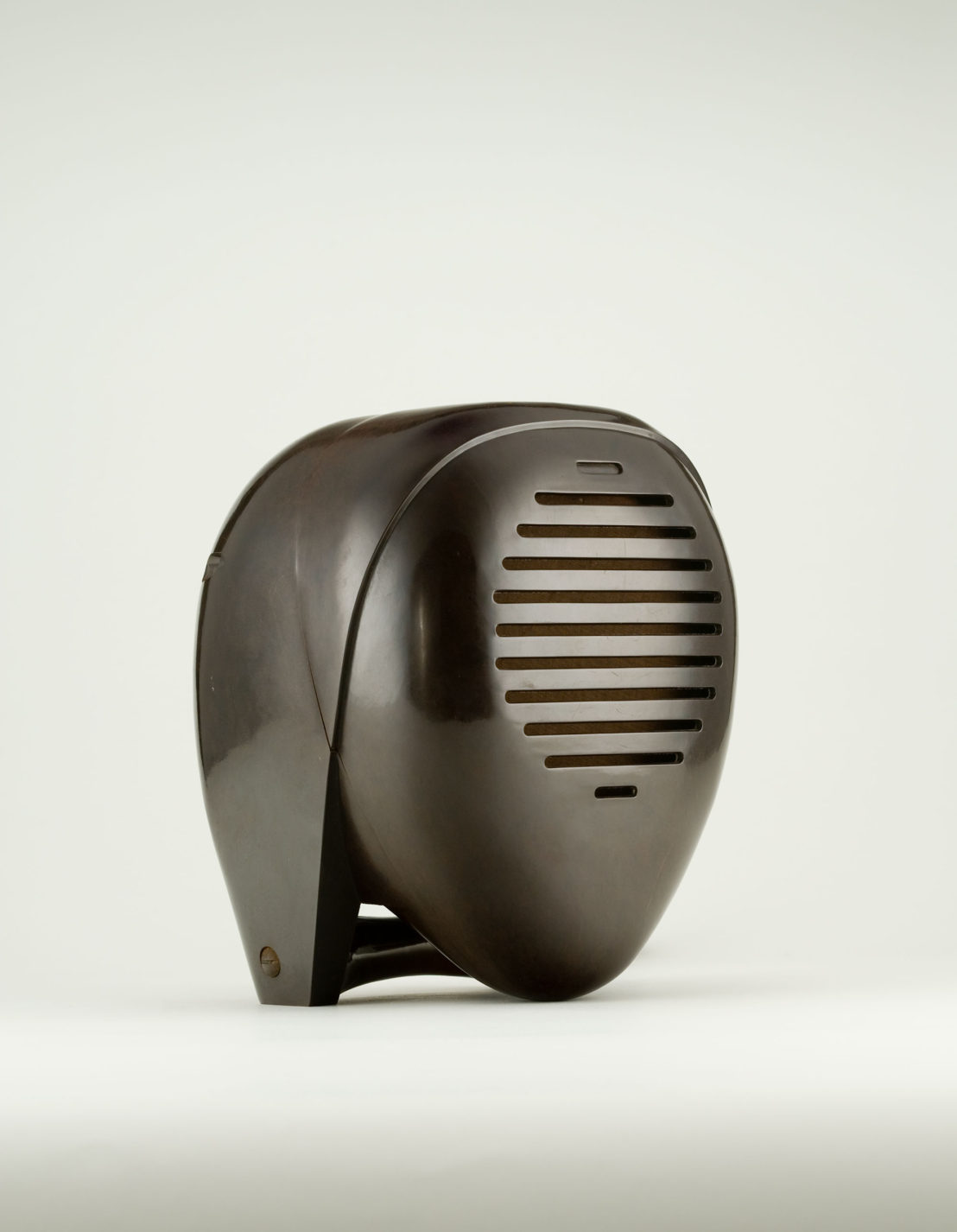 Radio receiver. Ovoid shaped speaker with a casing over the back, meant to look like an abstract head in an old-fashioned nurse's cap, and horizontal sound openings across the front.