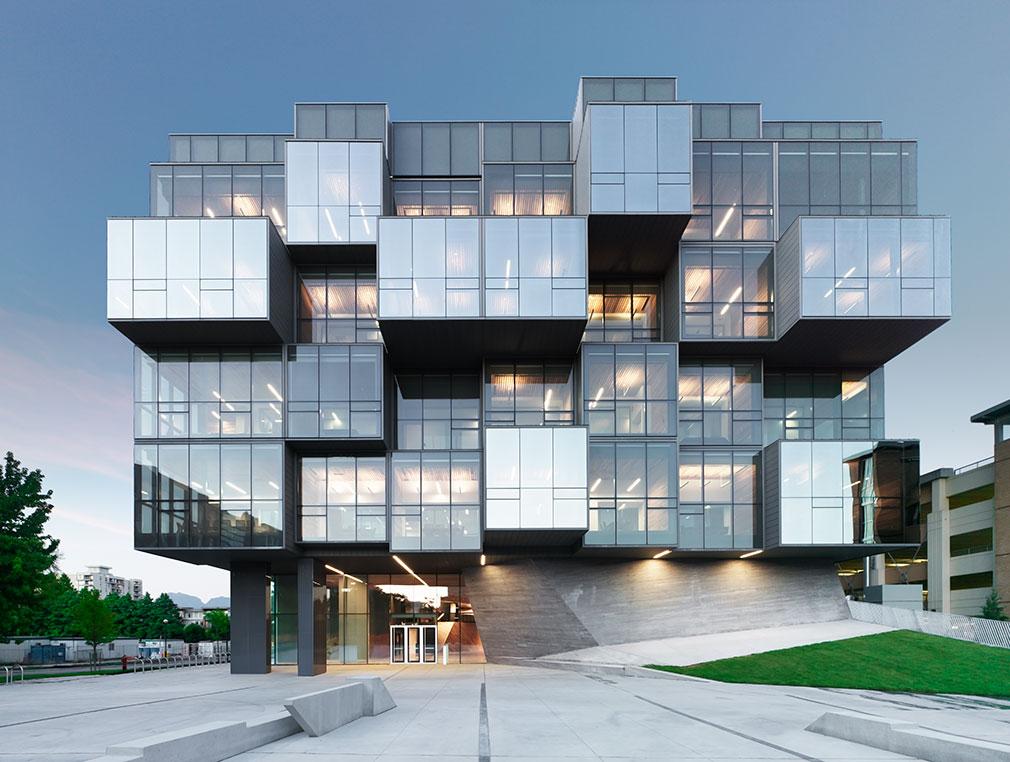 Bâtiment géométrique composé de blocs en verre saillants et encastrés déposés sur une base en béton.