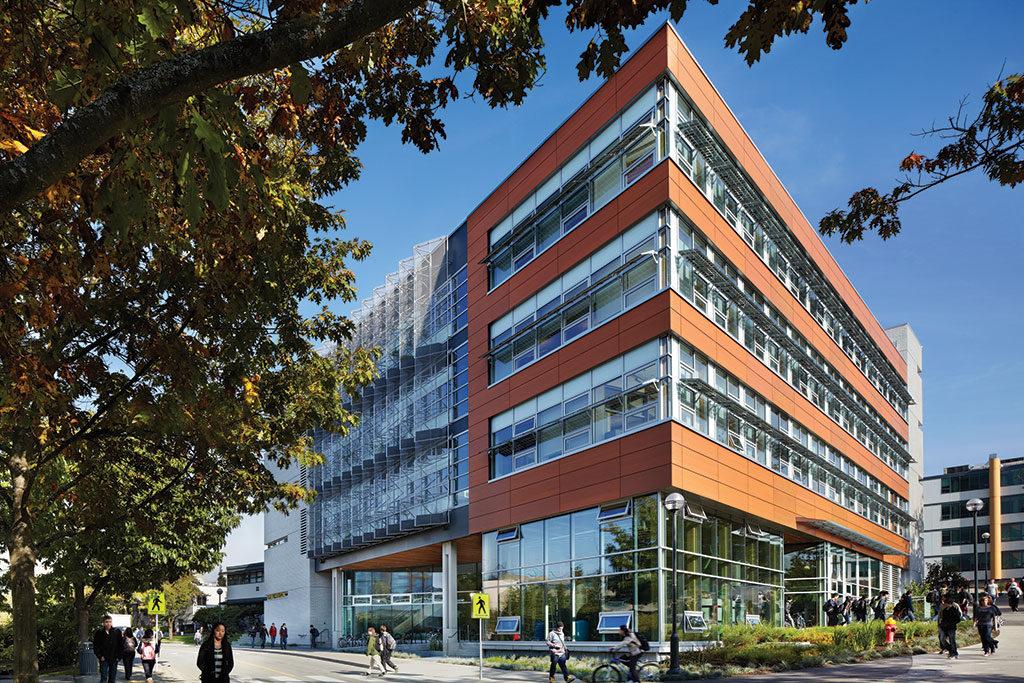 Bâtiment de quatreétages orné de rangées de fenêtres horizontales et d'accents de couleurs vives.