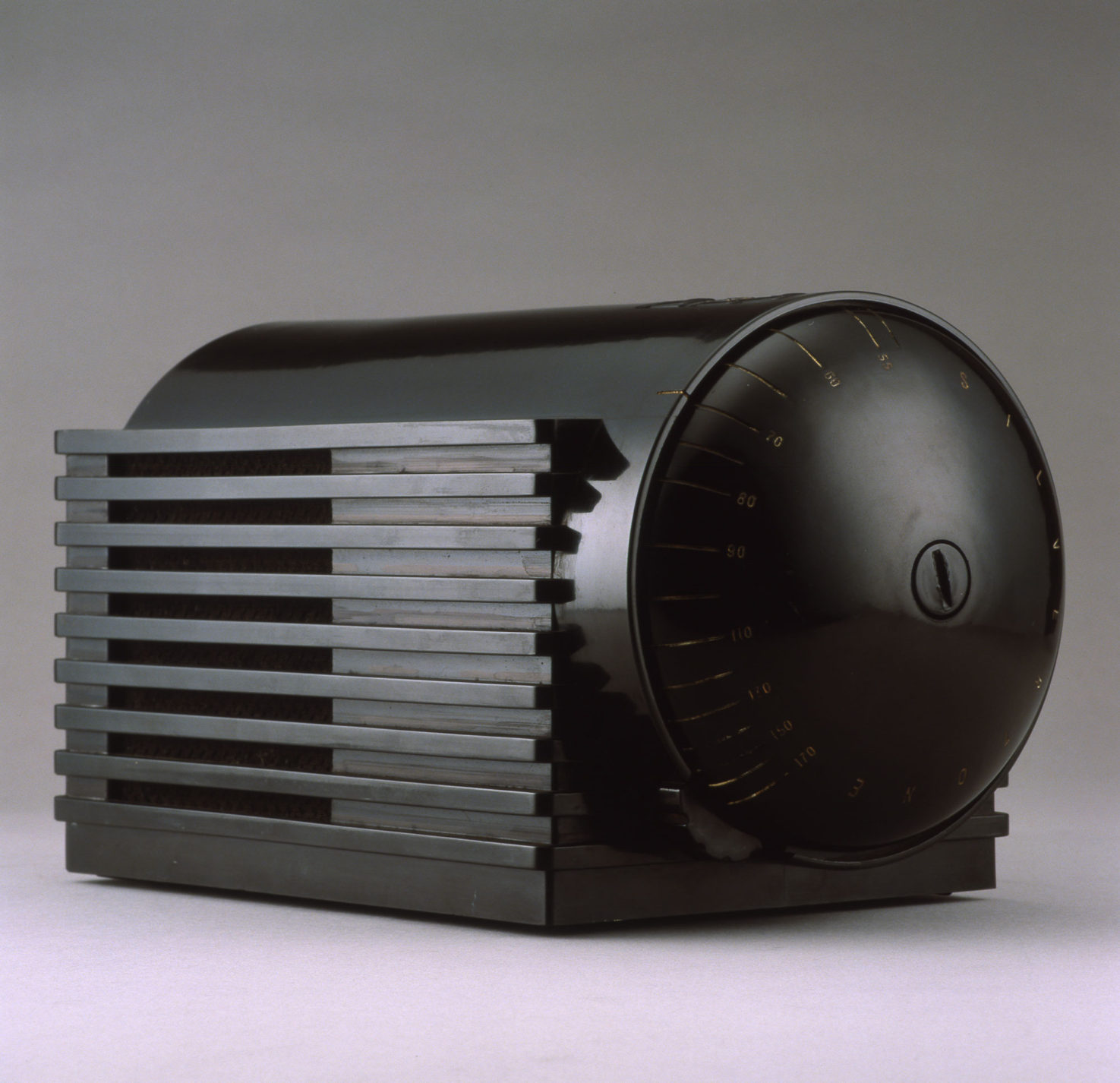 Black plastic radio with cylindrical body and rectangular base. One domed end of the body is the control dial.