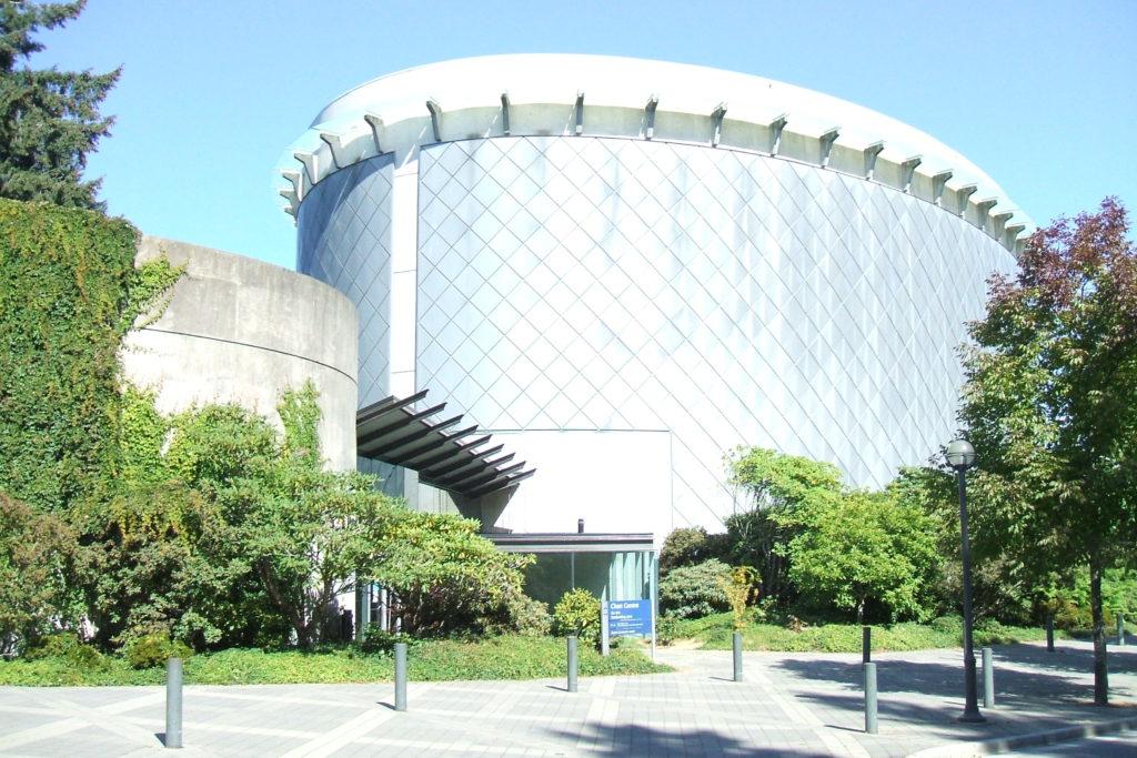 Structures jumelées en forme de tambour, entourées d'arbres et partiellement tapissées de lierre.