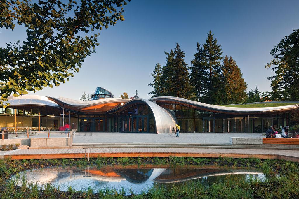 Bâtiment de plain-pied tout en courbes brillantes de métal et de verre surmonté d'un toit végétalisé ondulé.