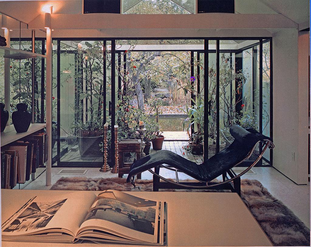 Pièce intérieure où trône une chaise longue; fenêtres du sol au plafond donnant sur un atrium.