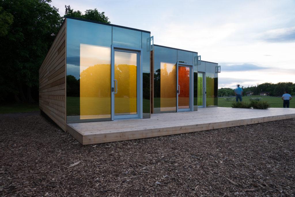 Trois conteneurs recyclés sur plateforme en bois forment ce bâtiment bas à façade de verre situé en bordure du parc.