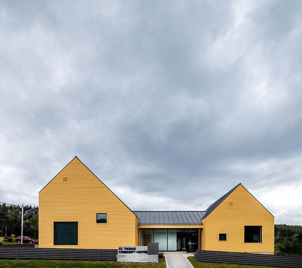 Bâtiment de plain-pied composé d'une entrée vitrée et de deux structures au toit très pentu de chaque côté.