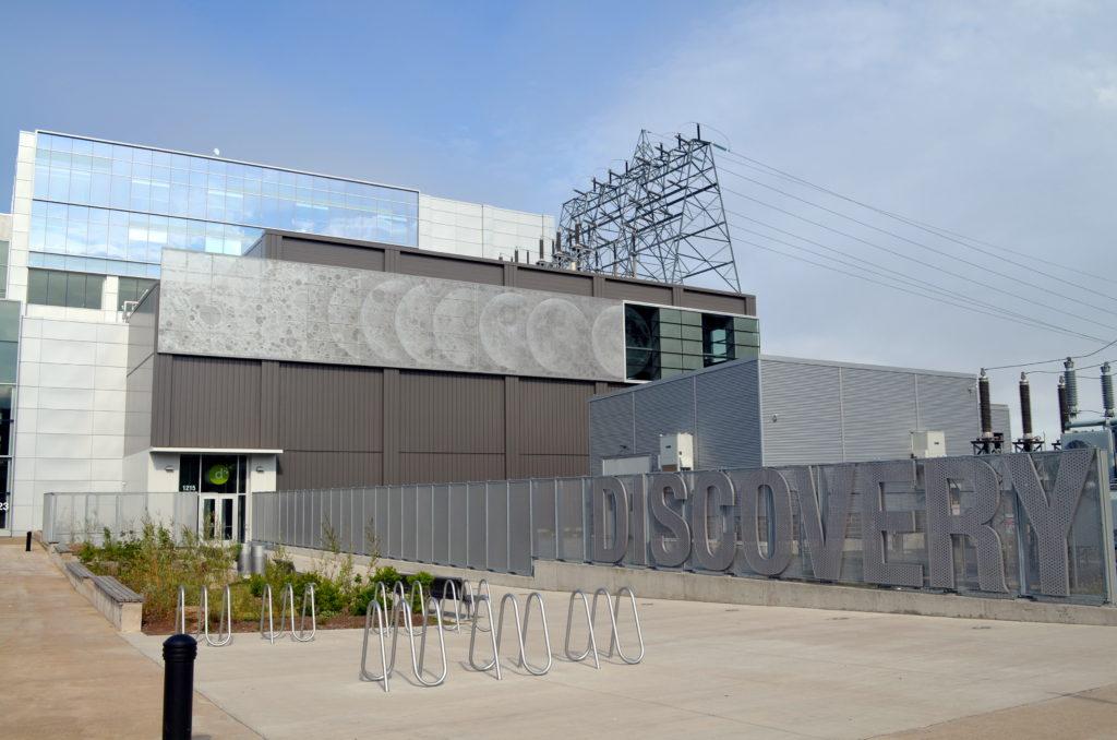 Bâtiment contemporain de trois étages composé de formes rectangulaires sécantes et superposées en béton, en métal et en verre.