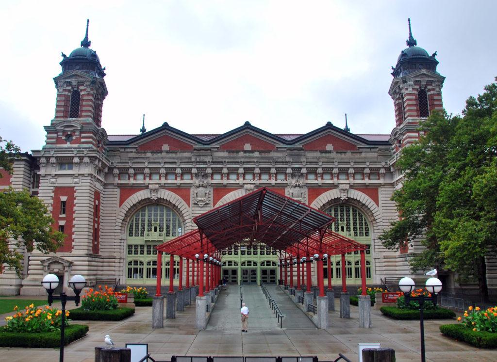 Bâtiment du début du XXesiècle flanqué de deux tours et pourvu d'un grand portail central en verre et en métal. Accents rouge vif et ferronnerie vert pâle.