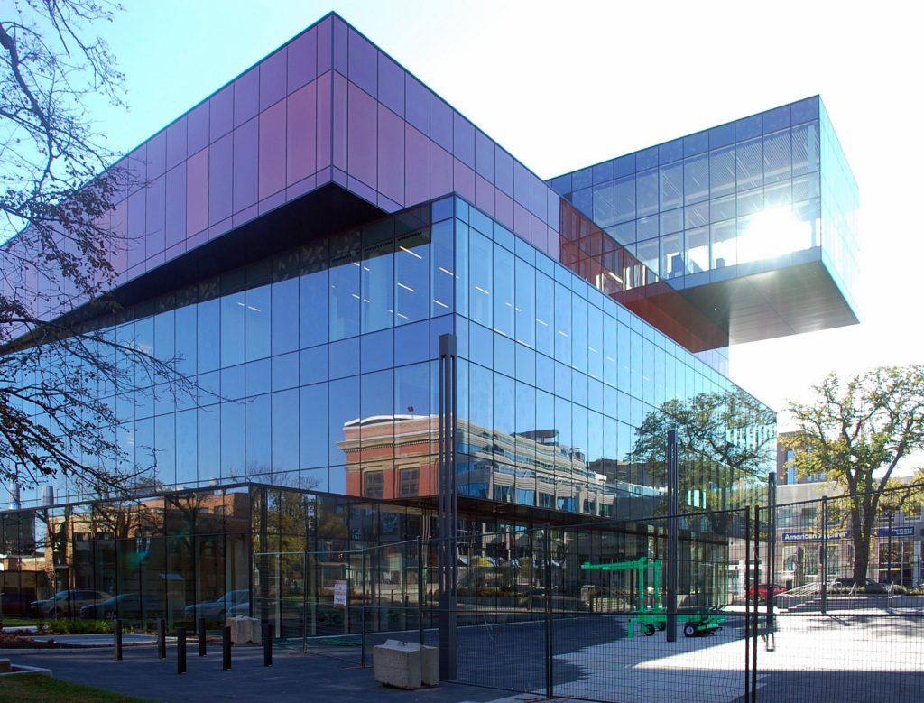Bâtiment de cinq étages composé de modules superposés de verre de différentes couleurs; module supérieur en porte-à-faux spectaculaire.
