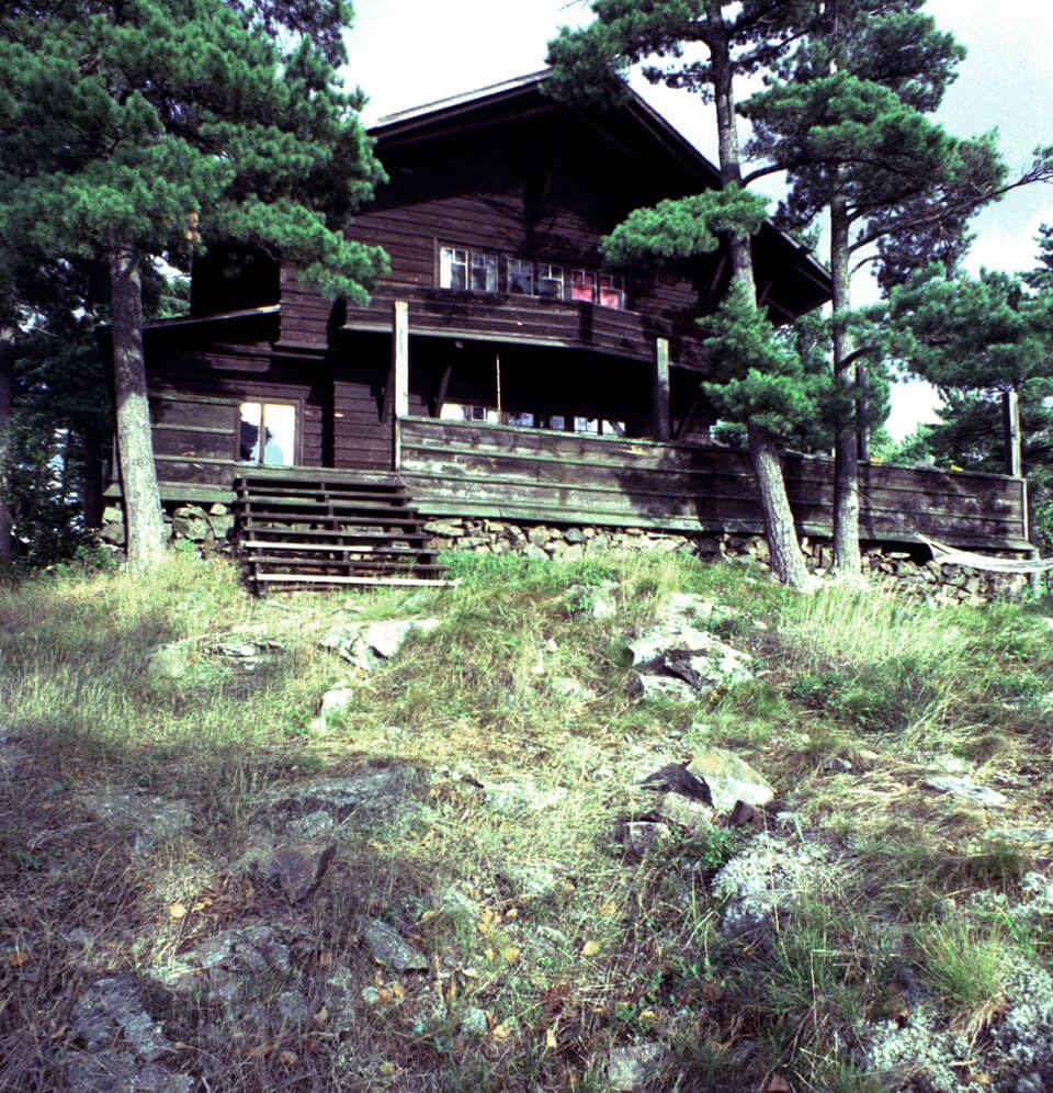 Shingled summer cottage with dark wood exterior, a tall pointed gable and a row of windows above a veranda on a rocky hill.