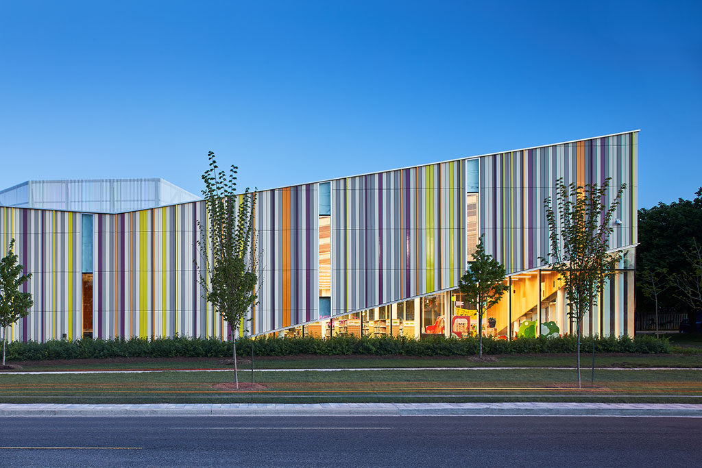 Horizontal building with sloping exterior walls of vertical slats in brightly colored glass.